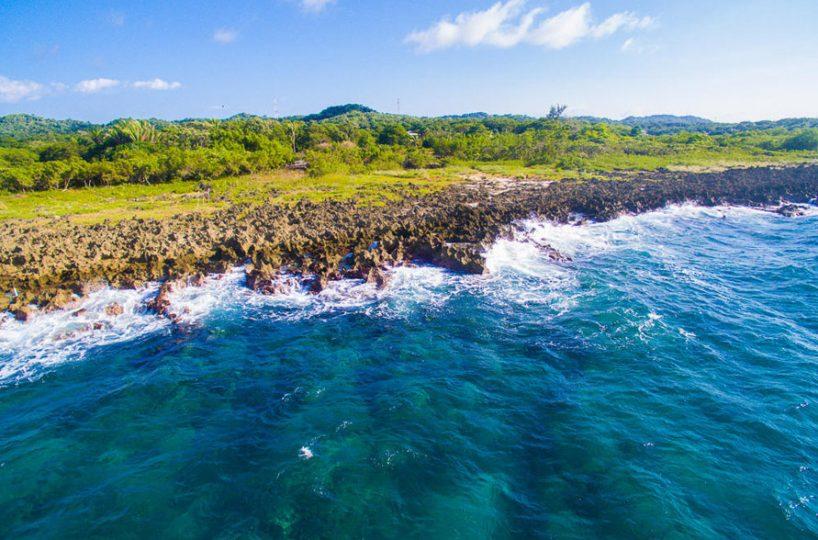 Dark iron shore divides the crashing waves and various hues of green on the Caribbean island of Roatan | Roatan Life Real Estate