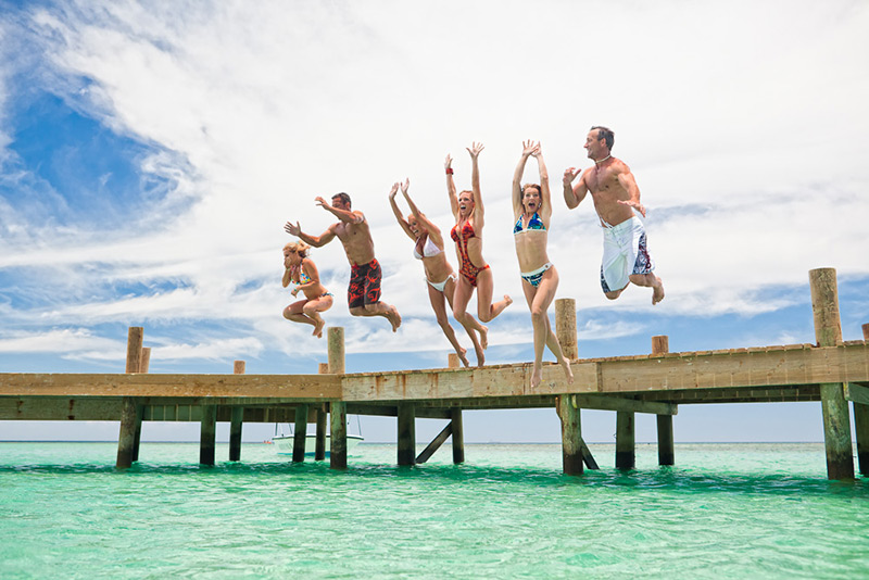 Friends jumping off a dock at the same time