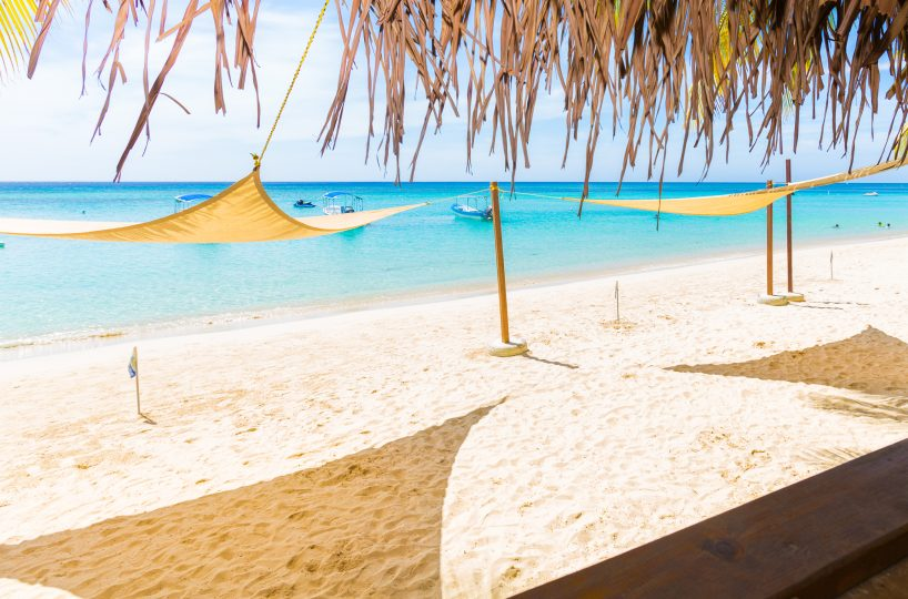 West Bay Beach on Roatan Island, bright sunshine hitting a thatched palapa roof and awnings for shade | Roatan Life Real Estate