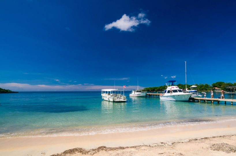 Three white boats and a long dock await passengers in Roatan | Roatan Life Real Estate
