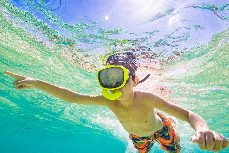 Young child snorkeling in a yellow mask and snorkel pointing out something out of view | Roatan Life Real Estate