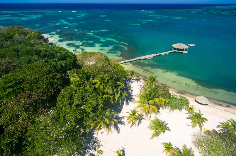 Aerial view of Palmetto Bay in Roatan, with a palapa and dock and a white sand beach in view | Roatan Life Real Estate