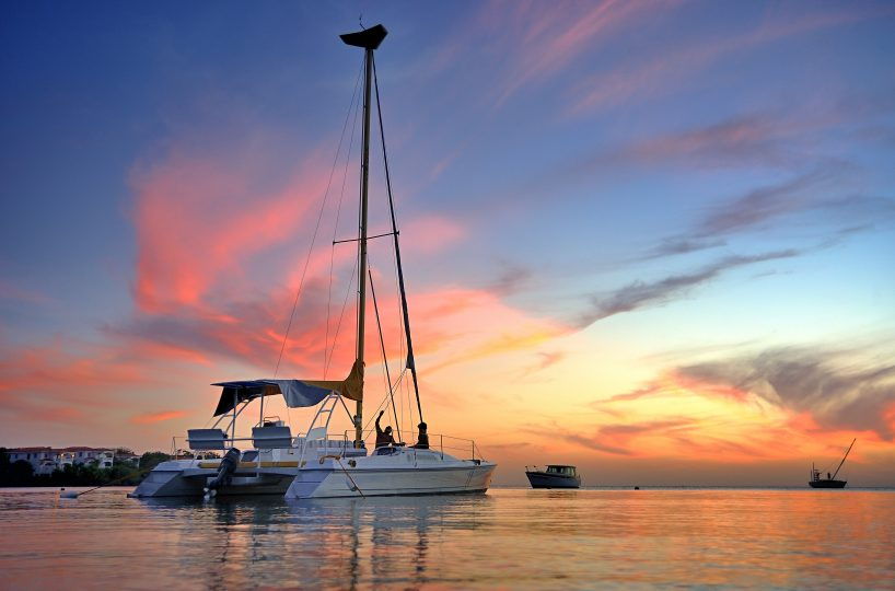 A multicolored sunset sky is the background for a large white catamaran with its sail down | Roatan Life Real Estate