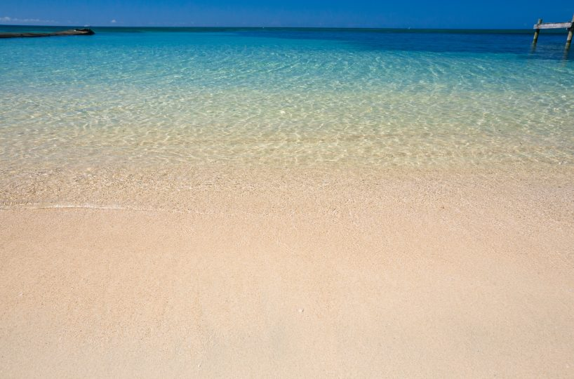 Clear tropical water gently lapping a smooth soft sand beach in Roatan | Roatan Life Real Estate