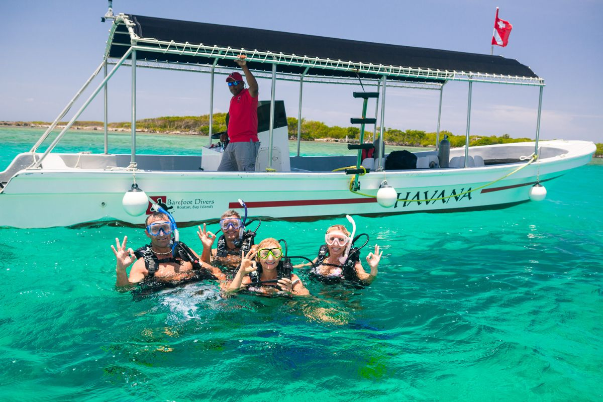 Divers in the water getting ready for a scuba dive in Roatan Honduras with their dive boat and captain beside them